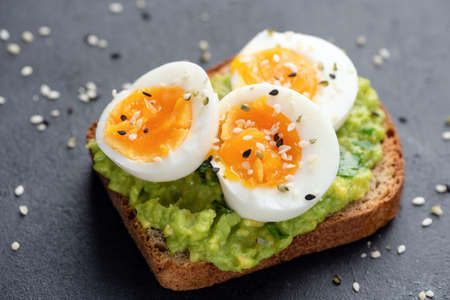 Toast with avocado and egg garnished with black and white sesame seeds. Healthy snack or breakfast food