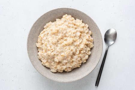 Oatmeal porridge, healthy breakfast food in a bowl. Boiled oats in bowl on grey concrete background, top view