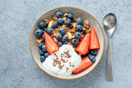 Healthy breakfast granola with berries and greek yogurt. Top view isolated bowl of whole grain cereals