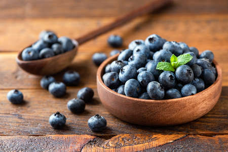 Blueberries in wooden bowl on a rustic wooden table. Healthy juicy summer berries