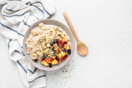 Healthy Oatmeal Bowl With Fruits Seeds Raisins On Grey Concrete Background. Top View Copy Space. Clean Eating, Healthy Breakfast Food Concept