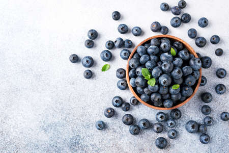Blueberries in bowl on concrete background. Top view with copy space for text. Organic blueberries harvest