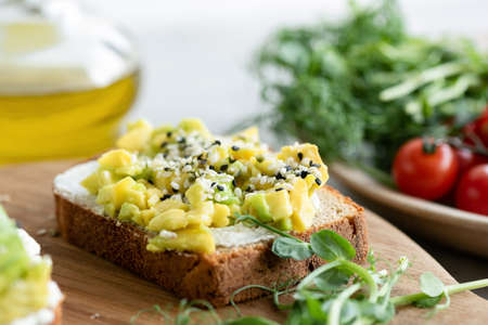 Bread toast with avocado, cream cheese and sesame seeds. Healthy breakfast or snack food