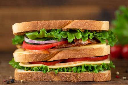 Club Sandwich with bacon cheese tomato lettuce. Tasty unhealthy sandwich