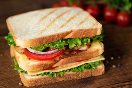 Club Sandwich with bacon cheese tomato lettuce. Tasty unhealthy sandwich