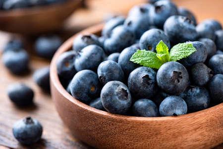 Blueberries in a wooden bowl, closeup view. Organic juicy berries Standard-Bild