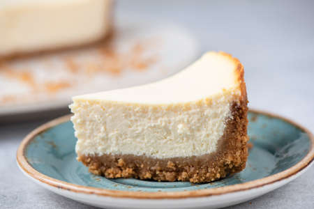 Slice Of Classical New York Cheesecake On A Blue Plate, Closeup View, Selective Focus