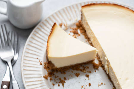 Classical new york cheesecake with slice cut out on a plate. Tasty cheesecake