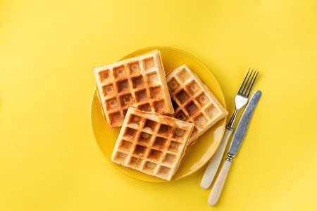 Belgian waffles on plate on yellow background. Isolated on yellow plate of sweet waffles