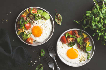 Sunny side up egg breakfast with avocado salad on plate, top view. Healthy breakfast food