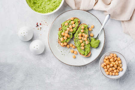 Vegan toasts with mashed avocado and chickpeas on a gray concrete background, top view. Healthy vegetarian avocado chickpea toasts garnished with hemp seeds