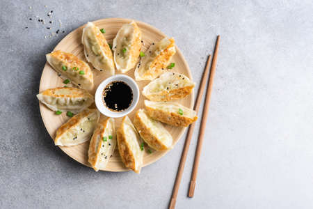 Gyoza fried chinese dumplings with chicken meat served with soy sauce on a bamboo plate. Top view of asian food gyoza dumpling