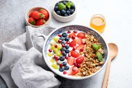 Yogurt granola bowl with berries strawberries pomegranate kiwi fruit blueberries closeup view. Healthy breakfast cereal granola bowl 版權商用圖片