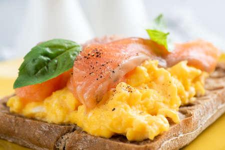 Scrambled egg and smoked salmon on a rye bread toast, closeup view. English breakfast food 版權商用圖片