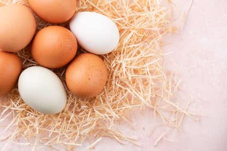 Chicken eggs on pink background top view. Organic chicken eggs