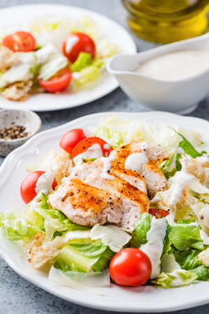 Caesar salad with grilled chicken, cherry tomatoes and sauce, closeup view