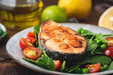 Roasted salmon steak with spinach salad