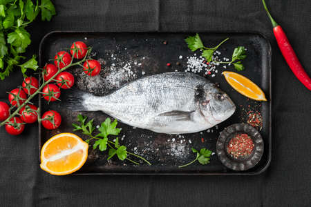 Raw uncooked dorado fish, spices and vegetables for cooking