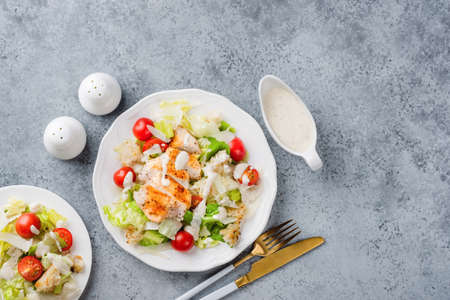 Chicken Caesar Salad With Dressing On White Plate