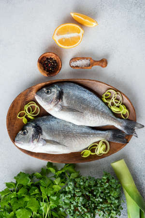 Fresh uncooked Dorado fish, salt, pepper and onion