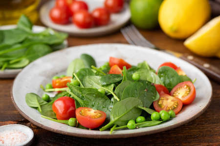 Healthy green salad with mini spinach, tomatoes and green peas
