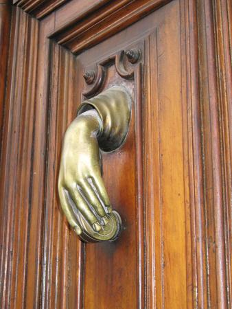 Door hand knocker old in a female hand, on the old wodden door.
