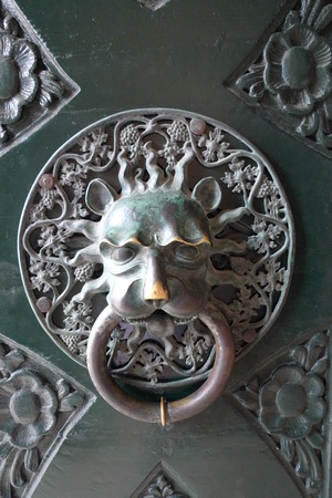 Old Door knoker. Door handle in the form of a lion's head. Detail of the shabby door.