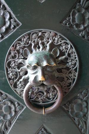 Old Door knoker. Door handle in the form of a lions head. Detail of the shabby door. Stock Photo