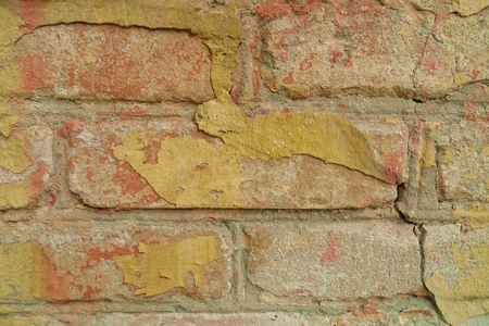Old yellow paint on a brick wall