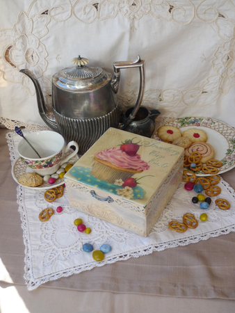 Retro still life with old teapot and a box of candy and cookies on a lace napkin.