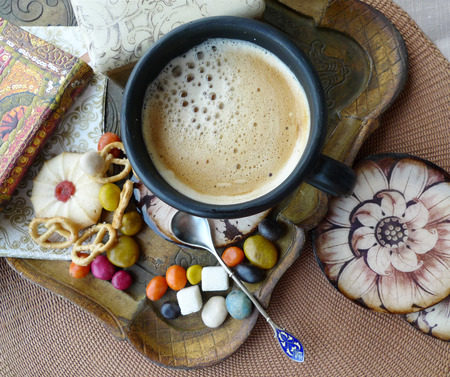 Retro still life. A cup of coffee with cream, biscuits and sweets on a tray. Decoupage. Stock Photo