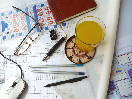 Business still life, background. Photo A glass of juice on the architectural drawings (horizontal) Objects: architectural drawing, PC mouse, diary, glass of juice, glasses, vellum and pencil. Photo taken on: May 20st, 2016