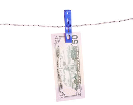 attached: Dollar bills hanging on rope attached with clothes pins. Money-laundering concept.