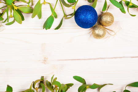 old fashioned christmas: Christmas background border with gold bauble decorations, holly, mistletoe, fir and cedar cypress greenery on old parchment paper. Stock Photo
