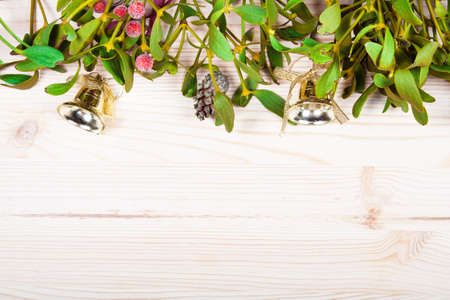 Christmas background border with gold bauble decorations, holly, mistletoe, fir and cedar cypress greenery on old parchment paper. Stock Photo