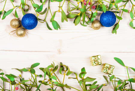 gold christmas decorations: Christmas background border with gold bauble decorations, holly, mistletoe, fir and cedar cypress greenery on old parchment paper. Stock Photo