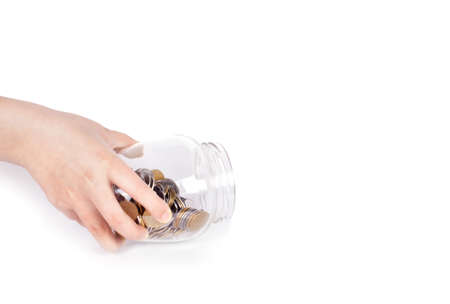 save: image of female hand putting a coin into glass bottle, saving concept Stock Photo