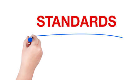 compliant: Standards word write on white background by woman hand holding highlighter pen Stock Photo