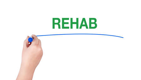 rehab: Rehab word write on white background by woman hand holding highlighter pen