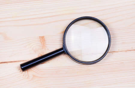 len: Magnifying glass on wood background, Search symbol