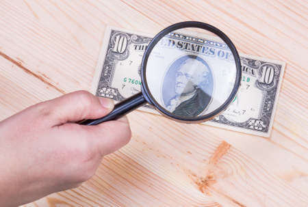 authentication: authentication of ten dollars banknote on wooden background Stock Photo