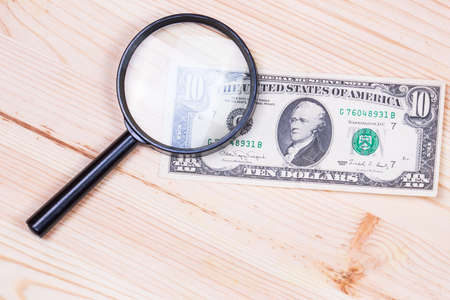 see the usa: authentication of ten dollars banknote on wooden background Stock Photo