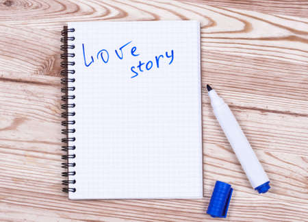 storytime: Book writing love story  and pen on wood desk