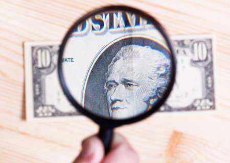 dinero falso: autentificación de diez dólares en billetes sobre fondo de madera