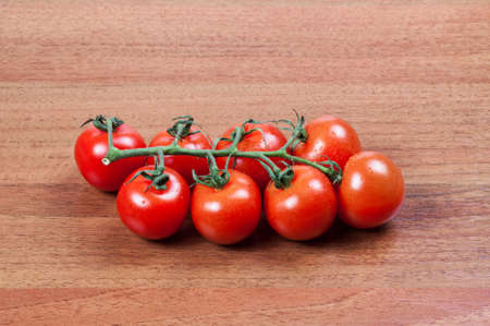 red color: Ripe cherry tomatoes on a wooden board