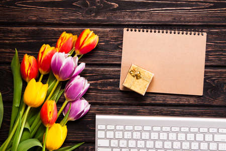lilac background: Tulips, keyboard and office supplies on a wooden board. View from above Stock Photo