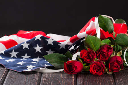 a memorial to fallen soldiers: Rose and american flag on wood background