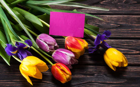 happy love: Tulips and a card on a wooden background