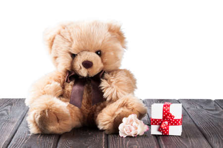 birthday background: Teddy bear and gift box on wood background