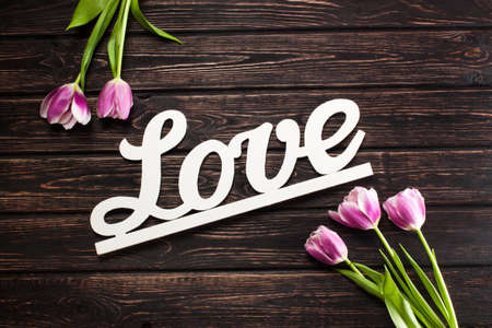 blossoming yellow flower tree: Inscription love and tulip on wood background